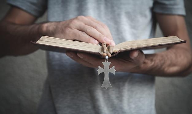 Homem caucasiano, rezando sobre a bíblia.
