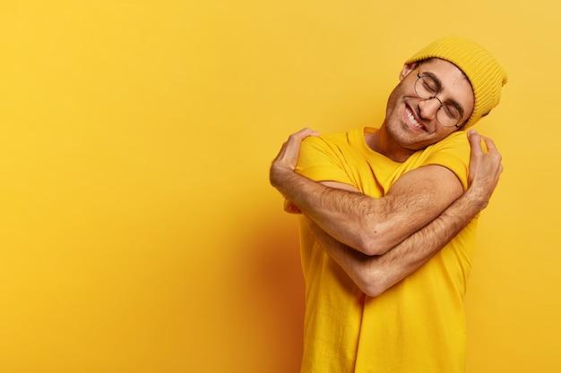 Homem caucasiano satisfeito se abraça, tem alta auto-estima, inclina a cabeça, tem um sorriso cheio de dentes, usa um chapéu amarelo casual e camiseta