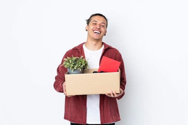 Homem caucasiano se mexendo enquanto apanha uma caixa cheia de coisas em uma parede branca isolada