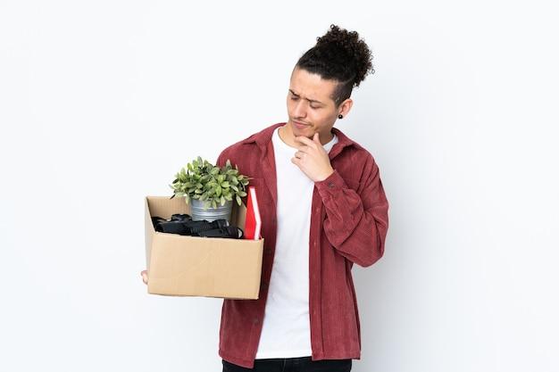 Homem caucasiano se mexendo enquanto apanha uma caixa cheia de coisas na parede branca isolada com uma expressão triste