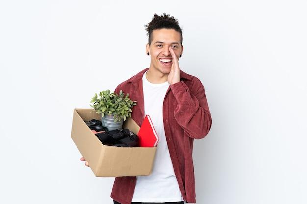 Homem caucasiano se mexendo enquanto apanha uma caixa cheia de coisas sobre uma parede branca isolada, gritando com a boca aberta