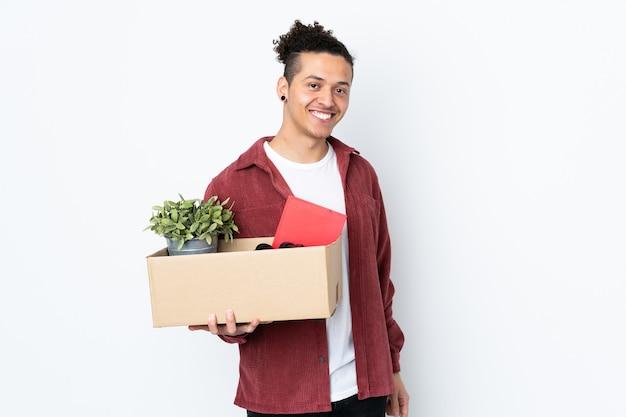 Homem caucasiano se mexendo enquanto pega uma caixa cheia de coisas na parede branca isolada sorrindo muito