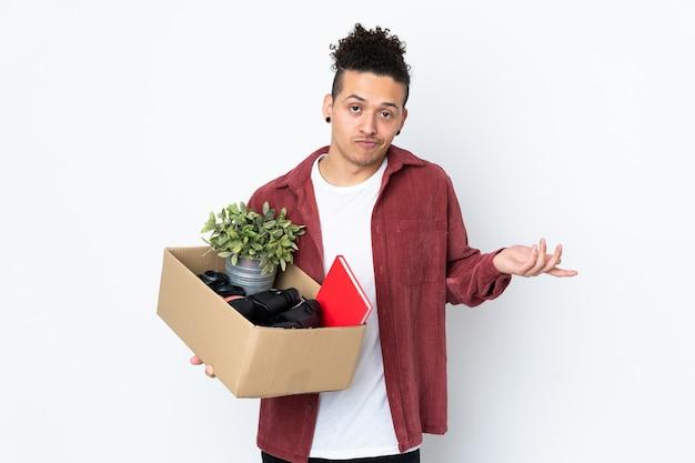 Homem caucasiano se mexendo enquanto pega uma caixa cheia de coisas sobre uma parede branca isolada, fazendo gestos de dúvida enquanto levanta os ombros