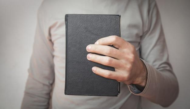 Homem caucasiano segurando a bíblia.