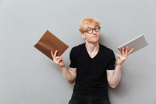 Homem caucasiano, segurando o livro e computador tablet.