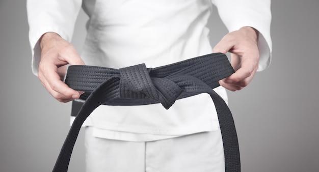 Homem caucasiano, segurando sua faixa preta. Foto Premium
