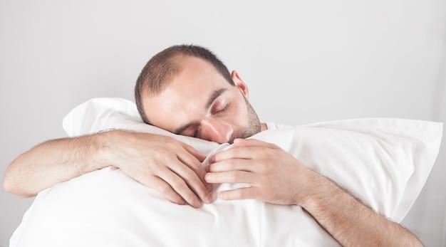 Homem caucasiano segurando travesseiro homem dormindo
