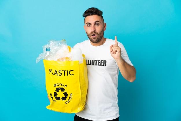 Homem caucasiano segurando um saco cheio de garrafas de plástico para reciclar isolado em um fundo azul com a intenção de perceber a solução enquanto levanta um dedo