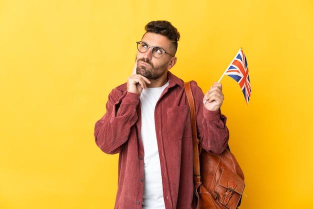 Homem caucasiano segurando uma bandeira do reino unido isolada em um fundo amarelo, tendo dúvidas e pensando