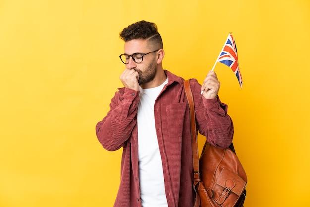 Homem caucasiano segurando uma bandeira do reino unido, isolada em um fundo amarelo, tendo dúvidas