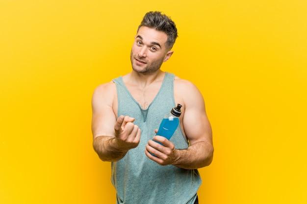 Homem caucasiano, segurando uma bebida energética, apontando com o dedo para você, como se estivesse convidando para se aproximar.