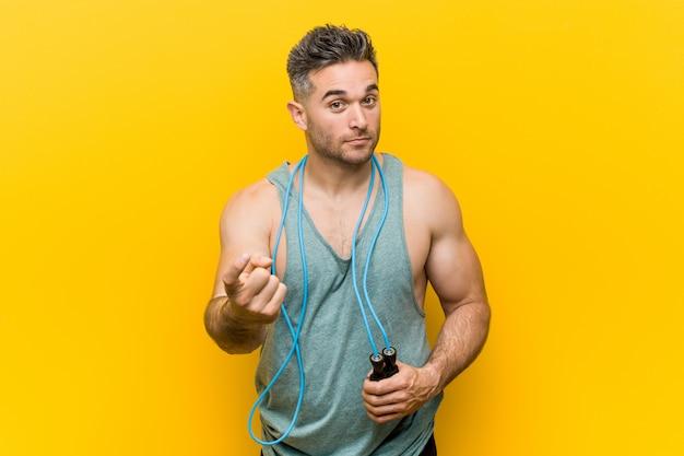 Homem caucasiano, segurando uma corda de pular, apontando com o dedo para você, como se estivesse convidando para se aproximar.
