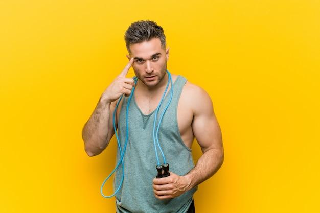 Homem caucasiano, segurando uma corda de pular, apontando seu templo com o dedo, pensando, focado em uma tarefa.