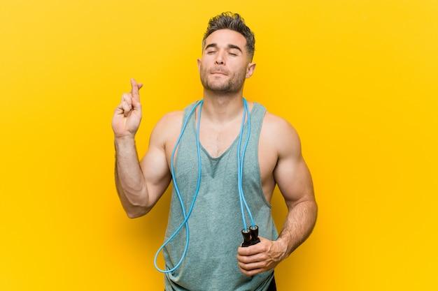 Homem caucasiano, segurando uma corda de pular cruzando os dedos por ter sorte