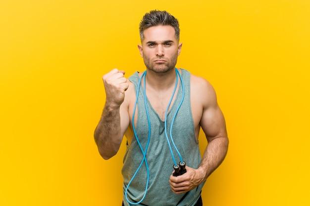 Homem caucasiano, segurando uma corda de pular, mostrando o punho, expressão facial agressiva.