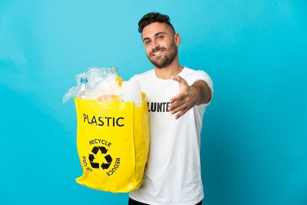 Homem caucasiano segurando uma sacola cheia de garrafas plásticas para reciclar isoladas em um fundo azul apertando as mãos para fechar um bom negócio