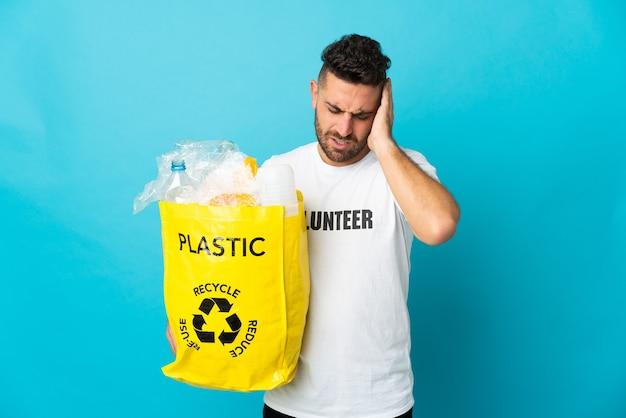 Homem caucasiano segurando uma sacola cheia de garrafas plásticas para reciclar isoladas em um fundo azul com dor de cabeça