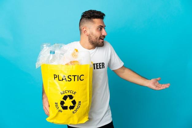 Homem caucasiano segurando uma sacola cheia de garrafas plásticas para reciclar isoladas em um fundo azul com expressão de surpresa enquanto olha para o lado