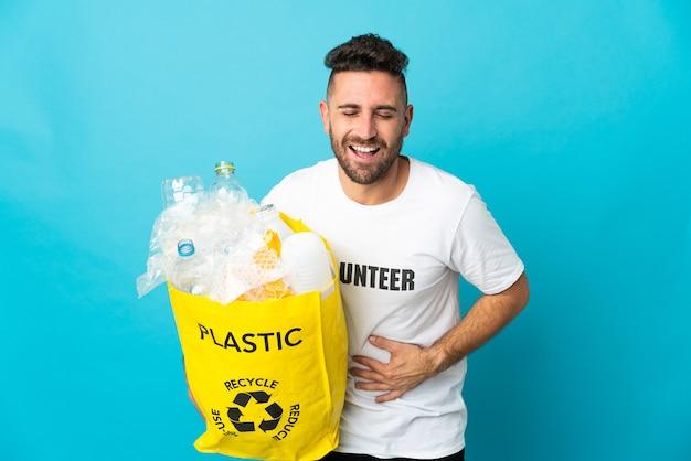 Homem caucasiano segurando uma sacola cheia de garrafas plásticas para reciclar isoladas em um fundo azul e sorrindo muito