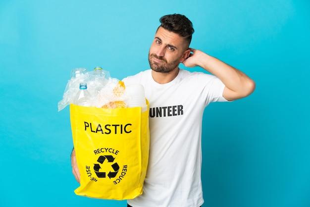 Homem caucasiano segurando uma sacola cheia de garrafas plásticas para reciclar isoladas em um fundo azul, tendo dúvidas