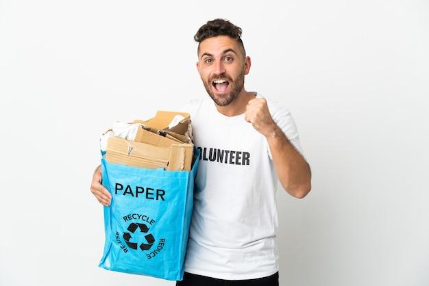 Homem caucasiano segurando uma sacola cheia de papel para reciclar, isolada no fundo branco, comemorando a vitória na posição de vencedora