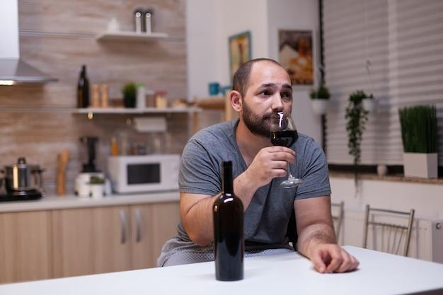 Homem caucasiano segurando uma taça de vinho, sentado na cozinha