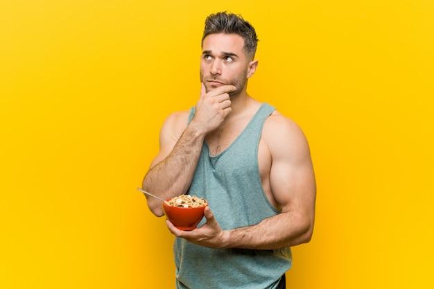 Homem caucasiano, segurando uma tigela de cereais, olhando de soslaio com expressão duvidosa e cética.
