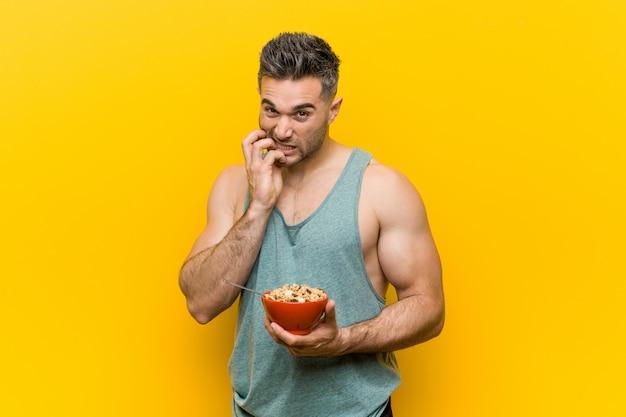 Homem caucasiano, segurando uma tigela de cereal, roer as unhas, nervoso e muito ansioso.