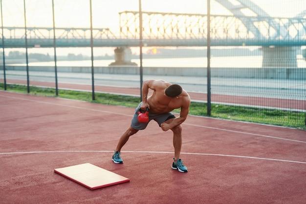 Homem caucasiano sem camisa, fazendo exercícios com kettlebell na quadra pela manhã.
