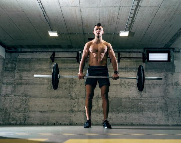 Homem caucasiano sem camisa, levantamento de pesos em pé no ginásio cross-fit.