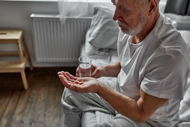 Homem caucasiano sênior doente tomando pílula e água potável, senta-se na cama sozinho. conceito de saúde e medicina