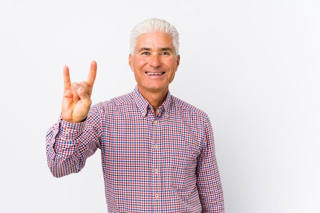 Homem caucasiano sênior isolado mostrando um gesto de chifres como um conceito de revolução.