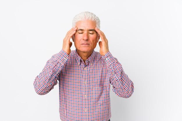 Homem caucasiano sênior isolado tocando templos e tendo dor de cabeça.