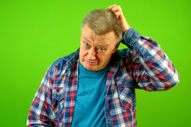 Homem caucasiano sênior perplexo e desnorteado, confuso, com expressão de camisa quadriculada e coçando a cabeça. ele duvida. fundo verde. fechar-se. dentro de casa.