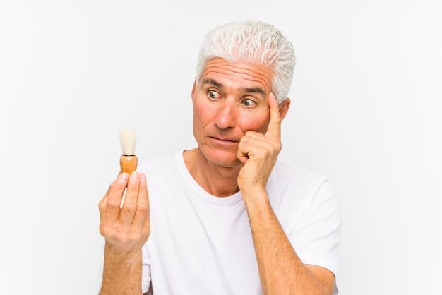 Homem caucasiano sênior raspou recentemente apontando sua têmpora com o dedo, pensando, focado em uma tarefa.