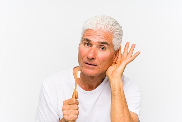 Homem caucasiano sênior segurando uma escova de dentes