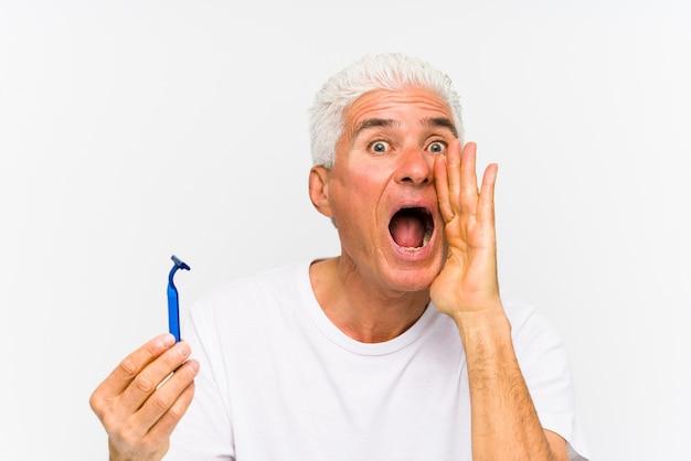 Homem caucasiano sênior segurando uma lâmina de barbear isolado gritando animado para a frente.