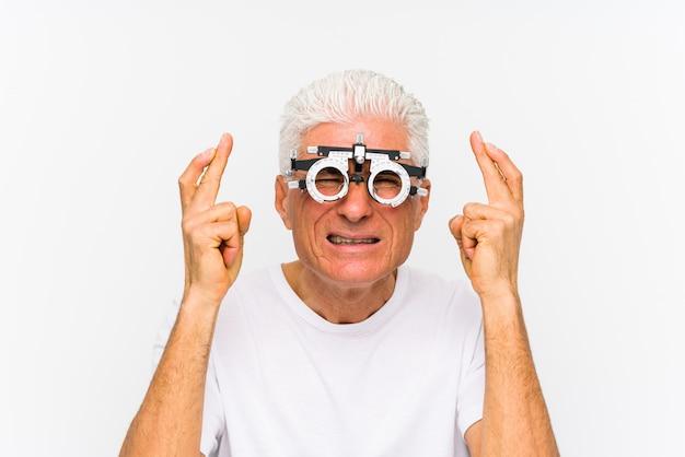 Homem caucasiano sênior, vestindo um quadro de julgamento optometrista, cruzando os dedos por ter sorte