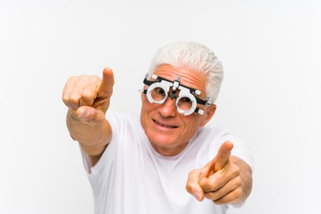 Homem caucasiano sênior, vestindo um quadro de julgamento optometrista, sorrisos alegres, apontando para a frente.