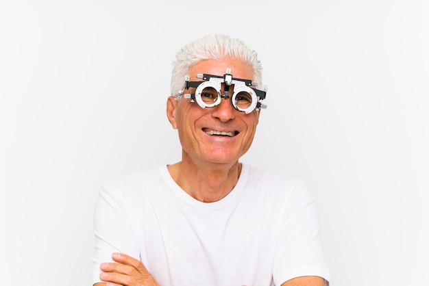 Homem caucasiano sênior, vestindo um quadro experimental de optometrista sorrindo confiante com braços cruzados.
