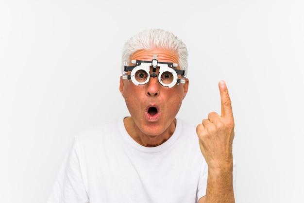 Homem caucasiano sênior, vestindo uma armação de julgamento de optometrista, tendo uma ótima ideia, o conceito de criatividade.