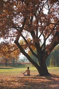 Homem caucasiano, sentado no asana e perfoming meditação no parque