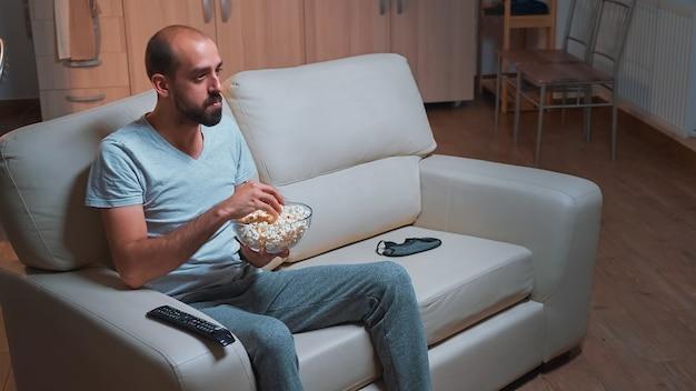 Homem caucasiano sentado no sofá com a tigela de pipoca nas mãos enquanto assiste a série de filmes