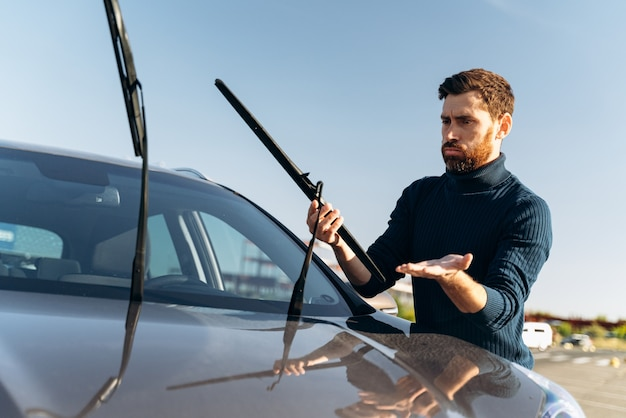 Homem caucasiano, sentindo-se confuso ao trocar os limpadores de para-brisa de um carro na rua durante o dia ensolarado. conceito de transporte