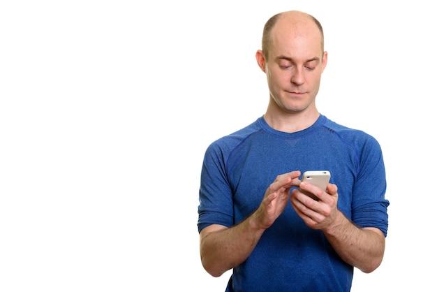 Homem caucasiano sério e careca usando telefone celular