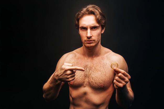 Homem caucasiano sério mostra preservativo na mão. jovem cara musculoso sexual com torso desportivo nu e olhando para a câmera. conceito de proteção sexual. isolado em fundo escuro. sessão de estúdio. copie o espaço