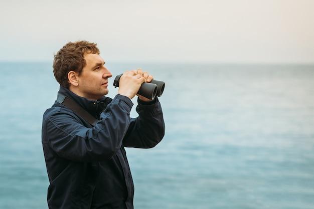 Homem caucasiano sobre o mar preparado para olhar através de binóculos