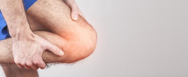 Homem caucasiano, sofrendo de dor no joelho.
