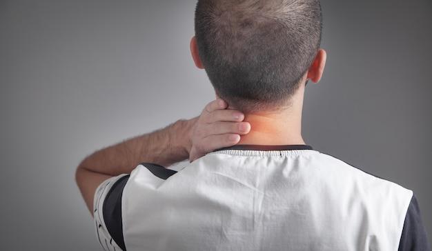 Homem caucasiano, sofrendo de dores no pescoço.