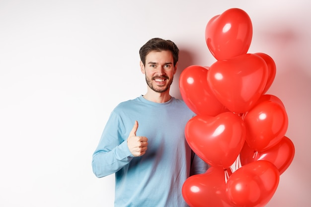 Homem caucasiano sorridente em pé com um balão de coração, prepara surpresa para o amante no dia dos namorados, mostrando os polegares para cima e olhando para a câmera, fundo branco
